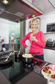 Portrait of happy senior woman with champagne glass cooking food in kitchen