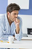 Young man coughing with coffee mug and medicine on kitchen counter