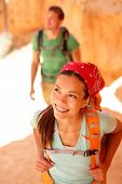 Hiking - Asian woman hiker in Bryce Canyon. Couple walking smiling happy together. Multiracial coupl