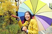 Fall / Autumn concept - woman excited under rain with umbrella. Beautiful young female wearing rainc