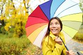 Autumn / fall - woman happy with umbrella in rain walking in forest. Girl enjoying rainy fall day looking away smiling. Mixed race Caucasian / Asian chinese girl.