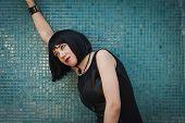 Pretty Goth Girl Posing Against A Blue Wall