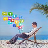 Young businessman on his beach chair using his laptop with colourful computer applications