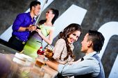 Two Asian young and handsome party people couples flirting and drinking at the bar in luxurious and
