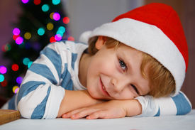 stock photo of sad christmas  - Little boy in santa hat with christmas tree and lights on background happy waiting for santa - JPG