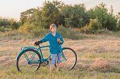 Teenager Boy With Retro Bike In Farm Field
