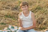 Teenage Boy In Farm Holds Glass Of Raw Milk