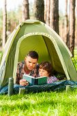 picture of tent  - Father and son reading book while lying in tent together - JPG