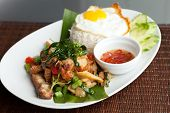 image of crispy rice  - Traditional Thai dish crispy pork with a fried egg atop the jasmine rice served with chili sauce - JPG