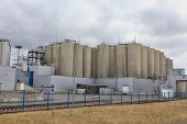 stock photo of silos  - Modern brewery yard with silos against cloudy sky - JPG