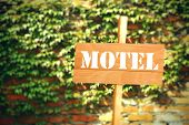 Signboard with text Motel on brick wall background