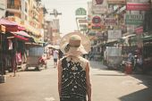 image of southeast asian  - A young woman wearing a hat is walking the famous backpacker street Khao San in Bangkok Thailand - JPG
