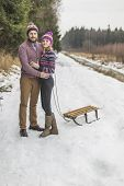 Young couple having a sled winter forest walk