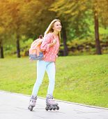 Fashion, Vacation And People Concept - Pretty Stylish Smiling Girl Rollerblading In The City Park
