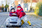 stock photo of rain  - Two happy sibling boys in red jackets and rain boots playing with big old toy car outdoors. Kids leisure on cold day in winter autumn or spring.