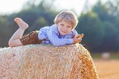 foto of hay bale  - Funny little kid boy in traditional German bavarian clothes leather shorts and check shirt lying on hay stack or bale and dreaming - JPG