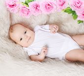Sweet Baby And Flowers On The Bed, Top View