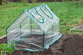 stock photo of collapse  - Frame collapsible mini greenhouses installed in the vegetable garden - JPG