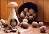 pic of nutcracker  - Wooden nutcracker and several walnuts on a wooden table - JPG