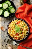 stock photo of saffron  - saffron rice with vegetables and cilantro on a dark wood background - JPG