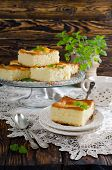foto of sponge-cake  - Cut the slices of sponge cake with pineapple rings on a wooden table - JPG