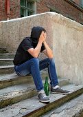 picture of sad man  - Sad Young Man on the landing steps with a Bottle of the Beer - JPG