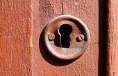 stock photo of keyholes  - very old keyhole in red wood door - JPG