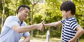 stock photo of promises  - asian father and elementary-age son sealing a deal or promise outdoors in a park.