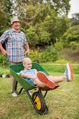 picture of wheelbarrow  - Happy grandfather and his granddaughter with a wheelbarrow in a sunny day - JPG