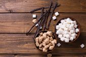 stock photo of sugar cube  - White and brown sugar cubes in bowsl and vanilla beans on dark painted wooden background - JPG