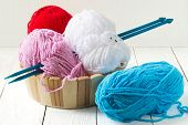 picture of knitting  - Colorful fluffy yarn for knitting and knitting needles in a basket on a white wooden background - JPG