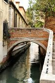 picture of arch foot  - Small Arched Foot Bridge over Narrow Canal Lined with Houses Venice Italy - JPG