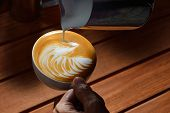 stock photo of latte  - Making of cafe latte art on the wooden table - JPG