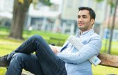 stock photo of sitting a bench  - Young gorgeous man sitting on bench in a park outdoor  - JPG