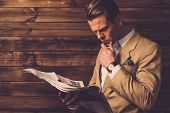 image of newspaper  - Stylish man with newspaper in rural cottage interior  - JPG