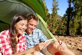 picture of woman couple  - Camping couple in tent using smartphone or small tablet looking at pictures photos - JPG