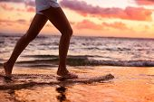 image of barefoot  - Running woman jogging barefoot in water at beach sunset - JPG