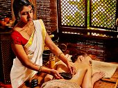 picture of panchakarma  - Young woman having Indian stone massage - JPG