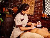 stock photo of panchakarma  - Man having compress ball ayurvedic spa treatment - JPG