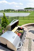 stock photo of barbecue grill  - Food arranged ready for grilling on an outdoor gas barbecue in a summer kitchen on a brick paved outdoor patio with a view of a lake in a healthy lifestyle concept - JPG