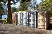 pic of defecate  - Portapotty or portable enclosed plastic portable toilet with chemicals and deodorizers in a tank in a park yard for public convenience - JPG