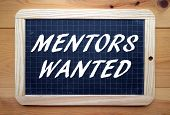 foto of mentoring  - The phrase Mentors Wanted in white text on a slate blackboard placed flat on a wooden surface - JPG