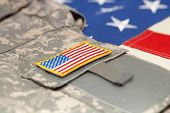 stock photo of army  - US flag with army uniform over it - studio shot