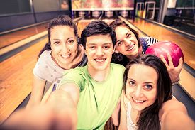 picture of selfie  - Group of friends at bowling taking a selfie - Young people having fun at bowling on a week-end meeting - Four young persons smiling and looking happy at camera