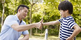picture of promises  - asian father and elementary-age son sealing a deal or promise outdoors in a park.