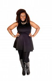 stock photo of tight dress  - A pretty African American woman standing in a black dress tights and boots smiling isolated for white background - JPG