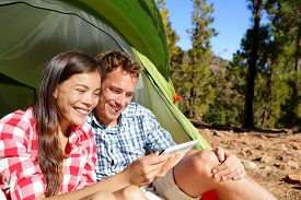 stock photo of camper  - Camping couple in tent using smartphone or small tablet looking at pictures photos - JPG