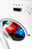 stock photo of washing machine  - Colorful shirt and trousers in a white laundry - JPG