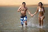 Man and woman running in the water hand in the hand