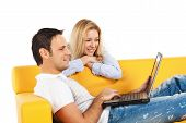 stock photo of computer-screen  - Happy young man and woman sitting together and looking at computer screen - JPG